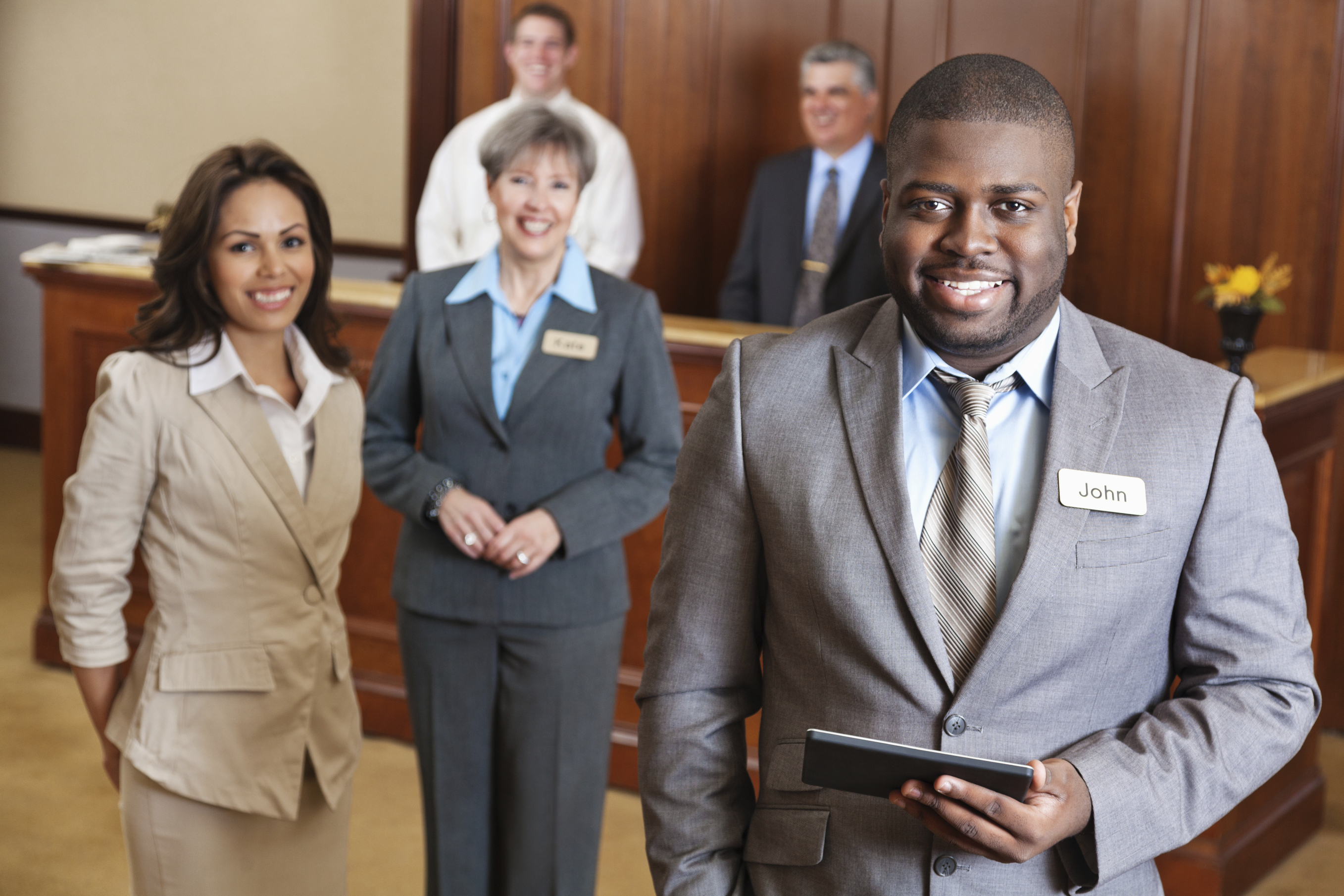 Hotel manager holding tablet with service team.